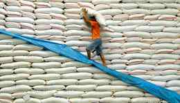 A National Food Authority (NFA) worker carries a sack of rice inside a warehouse in Manila.