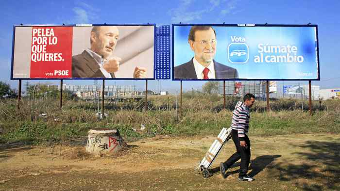 Juan Manuel Viedma, 27, an unemployed man who collects aluminium from garbage containers to sell it, walks past electoral posters of Prime ministerial candidate Alfredo Perez Rubalcaba (L) of the Spanish Socialist Workers' Party (Partido Socialista Obrero Espanol) and Spain's centre-right People's Party (Partido Popular) leader Mariano Rajoy in the Andalusian capital of Seville November 15, 2011.