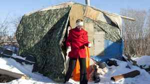 Interim NDP Leader Nycole Turmel steps out of a shelter being used as temporary housing in Attawapiskat, Ont., on Nov. 29, 2011.