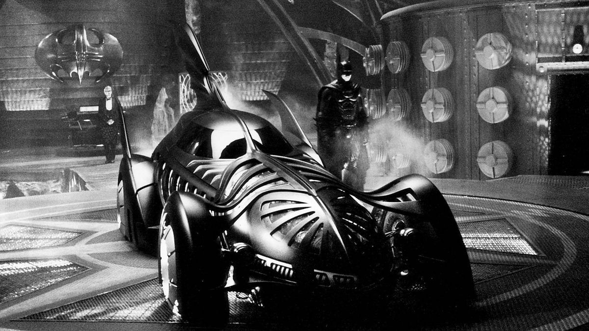 "Batman (Val Kilmer) prepares to take the Batmobile out to fight crime on the streets of Gotham City as his loyal butler, Alfred (Michael Gough), looks on in the 1995 film ""Batman Forever."""