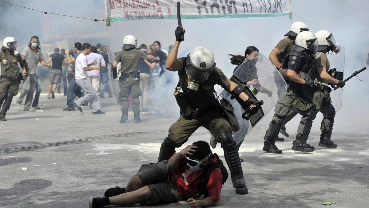 Protestors clash with riot police on June 15, 2011 during a demonstration near the parliament in the center of Athens. Thousands of demonstrators besieged the Greek parliament on June 15 in a large anti-austerity protest marred by violence, leaving at least a dozen injured ahead of a critical reform vote in parliament.