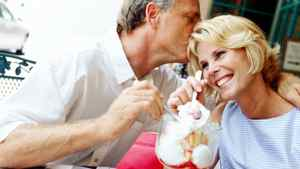 portrait of a mature couple sharing a sundae and kissing at a caf+??