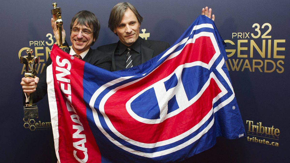 Director Philippe Falardeau, left, of the film Monsieur Lazhar and actor Viggo Mortensen of the film A Dangerous Method hold their Genie awards behind a Montreal Canadiens flag.