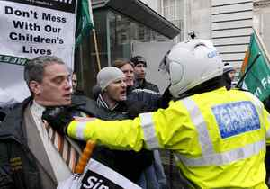 A motorbike police officer holds back Sinn Fein protesters who broke through the gates at government buildings, Dublin, Ireland, Monday, Nov. 22, 2010. The Sinn Fein protesters were calling for the Irish Prime Minister to resign. Ireland's banks will be pruned down, merged or sold as part of a massive EU-IMF bailout, the government says as a shellshocked nation comes to grips with its failure to protect its financial institutions. (AP Photo/Peter Morrison)