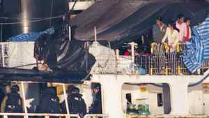 Some the estimated 490 people thought to be Tamil migrants aboard the ship MV Sun Sea peer out from underneath a tarp after Canadian Border officials and police brought the ship into Canadian Forces Base Esquimalt in Colwood, British Columbia on Vancouver Island August 13, 2010.