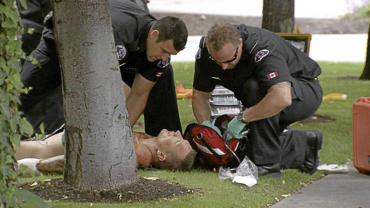 Paramedics assist a man who was injured in a gang - related shooting outside a casino in Kelowna, B.C. on Sunday, Aug. 14, 2011.