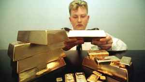 A security guard watches a stack of display gold bullion bars at the Australian Bullion Co.'s office in Sydney