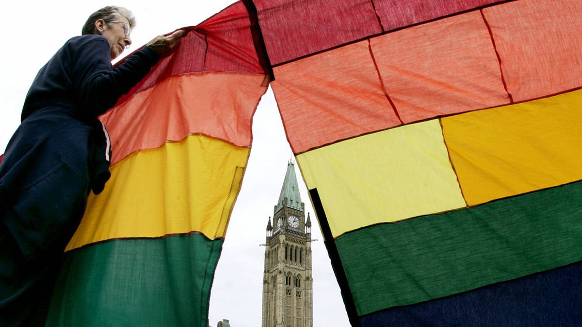 Silvie Small holds up a section of a 500 foot (152 meter) rainbow flag around Parliament Hill in support of same-sex marriage in Ottawa, June 19, 2005.