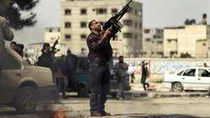 A Palestinian fires a weapon into the air during the funeral of Islamic Jihad militant Mohammed Daher in Gaza City on March 13, 2012.