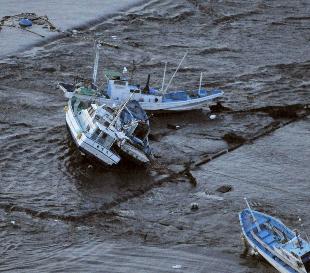 Fishing boats get stranded on shore at Oarai town, Ibaraki prefecture, Japan, after a ferocious tsunami spawned by one of the largest earthquakes ever recorded slammed Japan's eastern coasts on March 11, 2011.