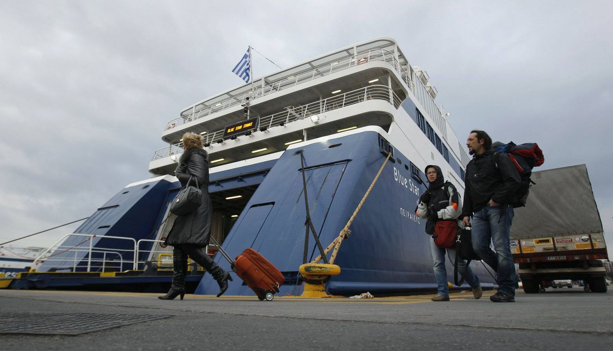 Passengers make their way in front of an immobilised ship at Piraeus port near Athens February 10, 2012. Greece's two major labour unions called a 48-hour strike for Friday and Saturday against the planned reforms by Greece's coalition government.