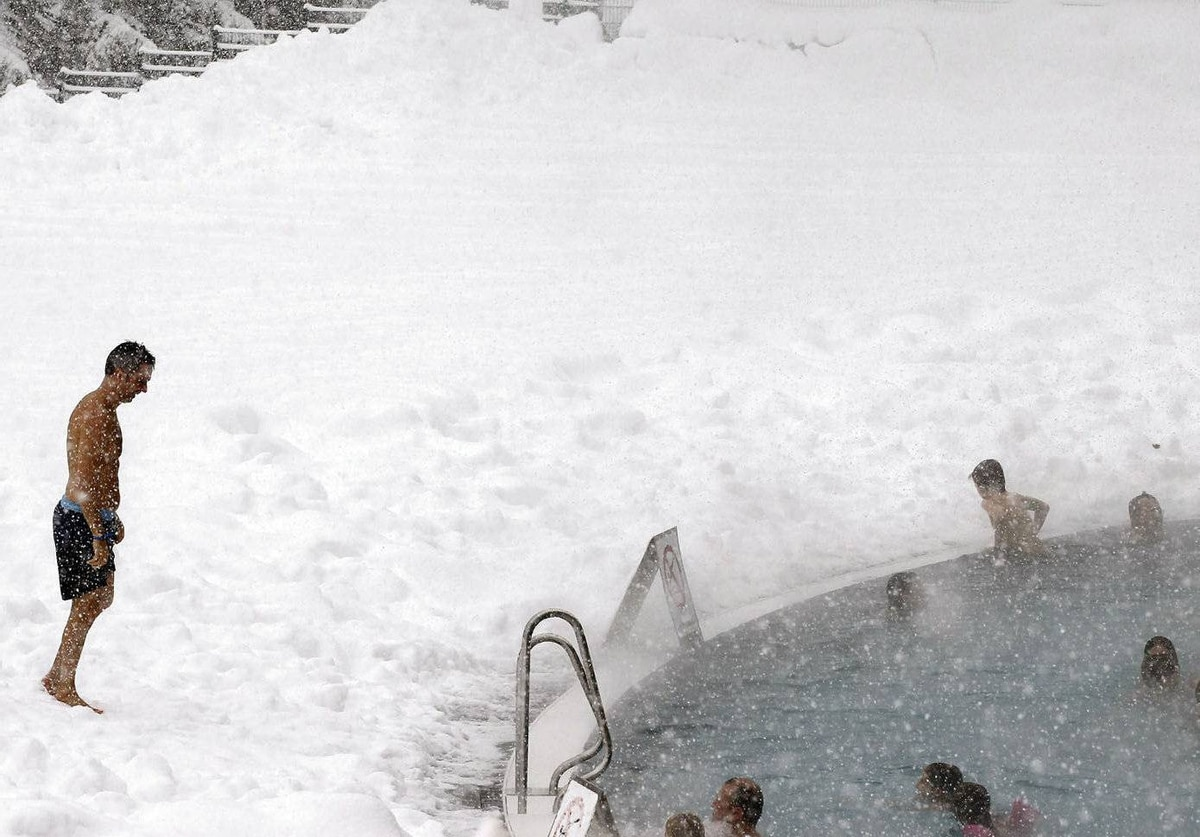 People relax in a public swimming pool as snow falls in the Swiss mountain resort of Davos.