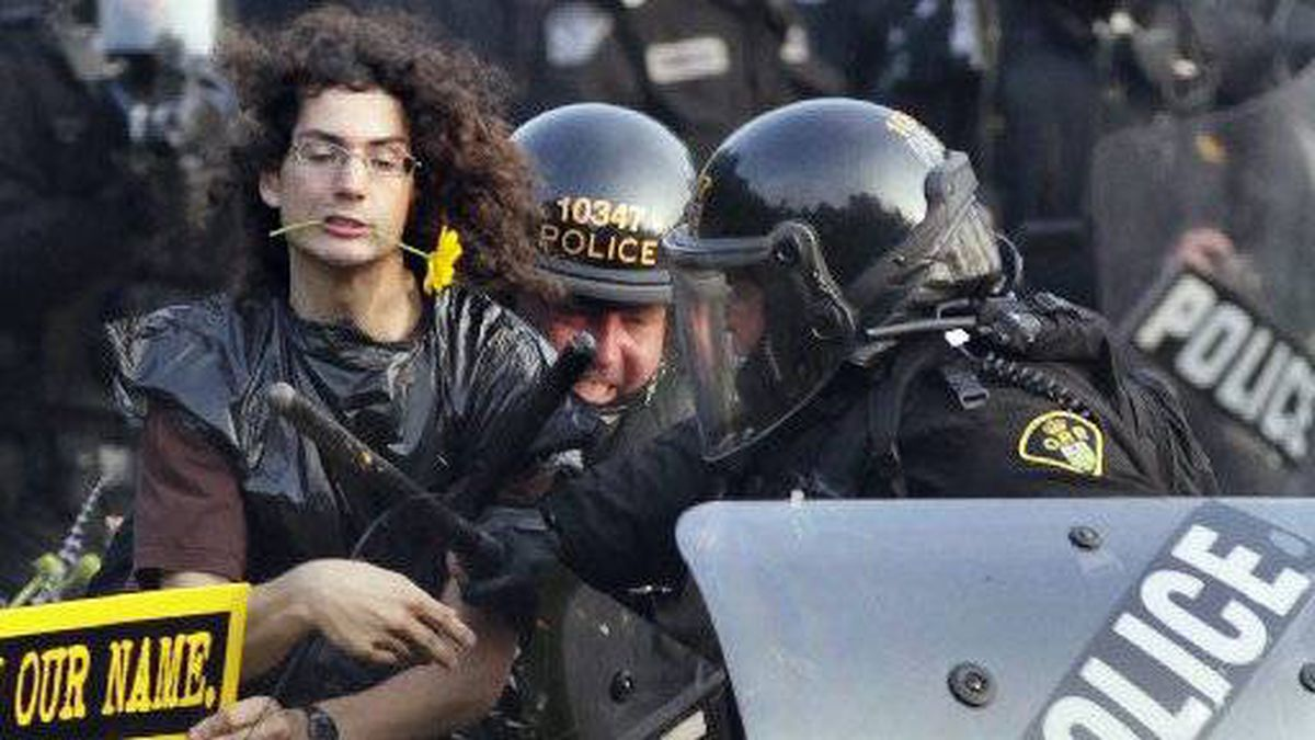 In this June 27, 2010,photo, a protester with a daisy clenched in his teeth is seized by riot police during protests at the G8 and G20 summits in Toronto.