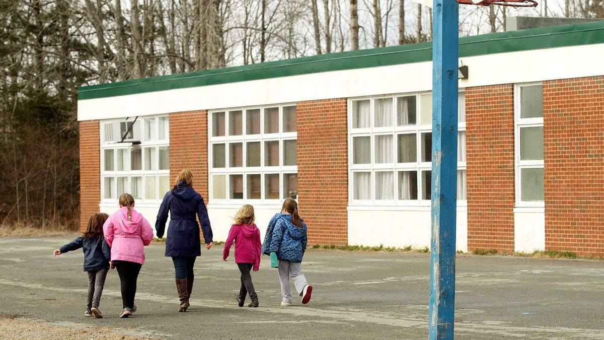 A teacher walks back to class with students after recess at the Newport Station District school.