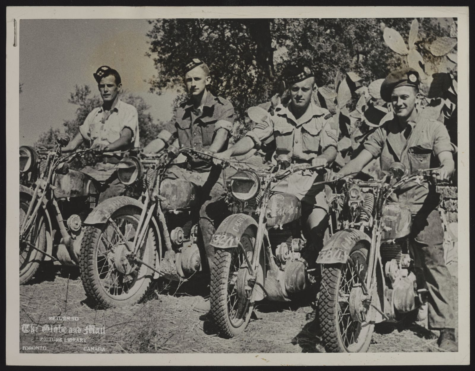 WORLD WAR II CANADA FORCES IN ITALY 23013- STURDY MOTORCYCLES TOOK MESSAGES THROUGH IN SICILY Stress laid on motorcycle maintenance by the Army paid dividends for these Canadian dispatch riders whose daring combined with mechanically perfect mounts to win a deadly game from Axis snipers on tortuous Sicily terrain. Establishment of a mobile motorcycle maintenance school is the latest step to verse Canadian troops in motorcycle mechanics. Dispatch riders pictured in Sicily are, left to right, Pte. J.C. Owen, Port Colbourne, Ont., Pte. E. Cooper, Toronto, Sgt, R.V. Dooley, Toronto, and L/cpl. B.E. MacDonald, Toronto, all of the 48th Highlanders of Toronto. (CANADIAN ARMY OVERSEAS PHOTO)