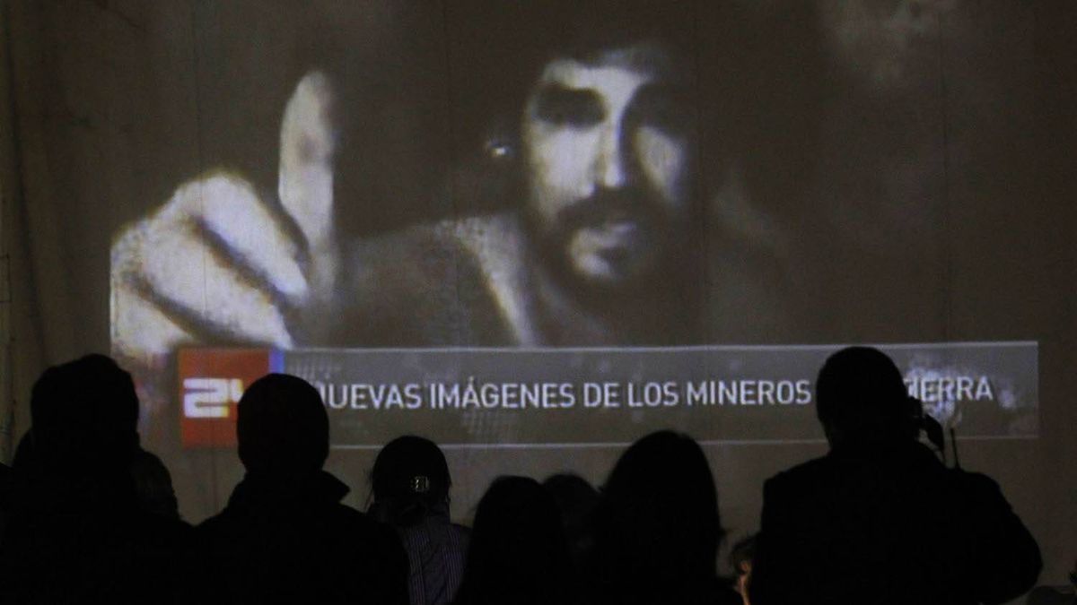 Relatives of the miners trapped underground gather around a screen that shows the miners inside the mine at Copiapo, Chile. Ivan Alvarado/Reuters