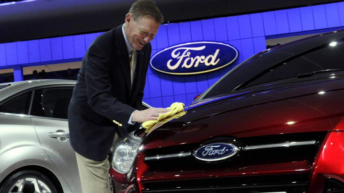 Ford CEO Alan Mulally shines the hood of a Ford Focus.
