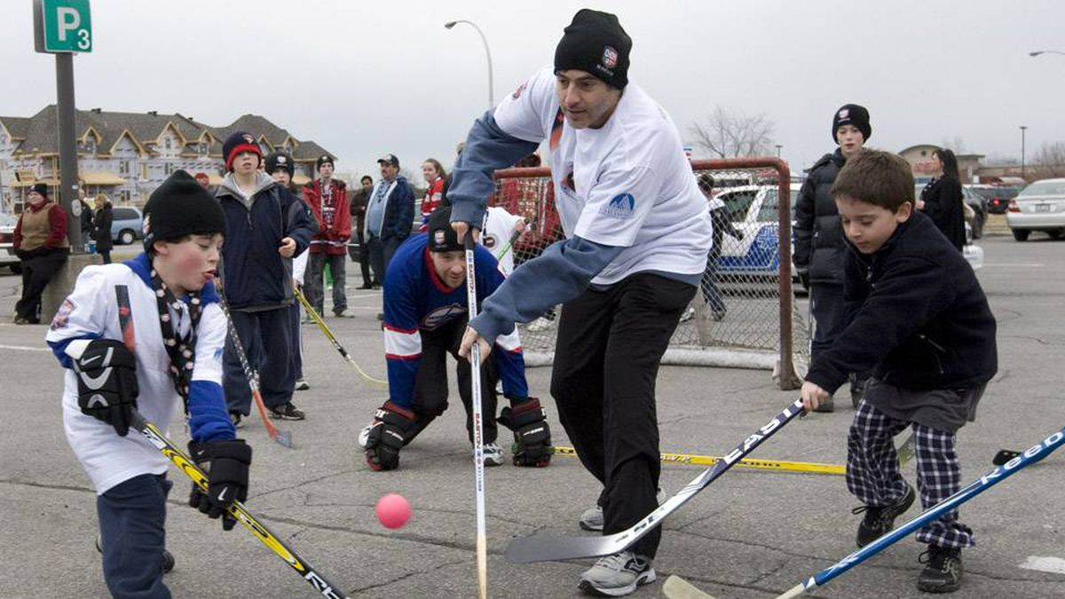 David Sasson, centre, received a $75 fine after refusing to break up a street hockey game in Montreal.