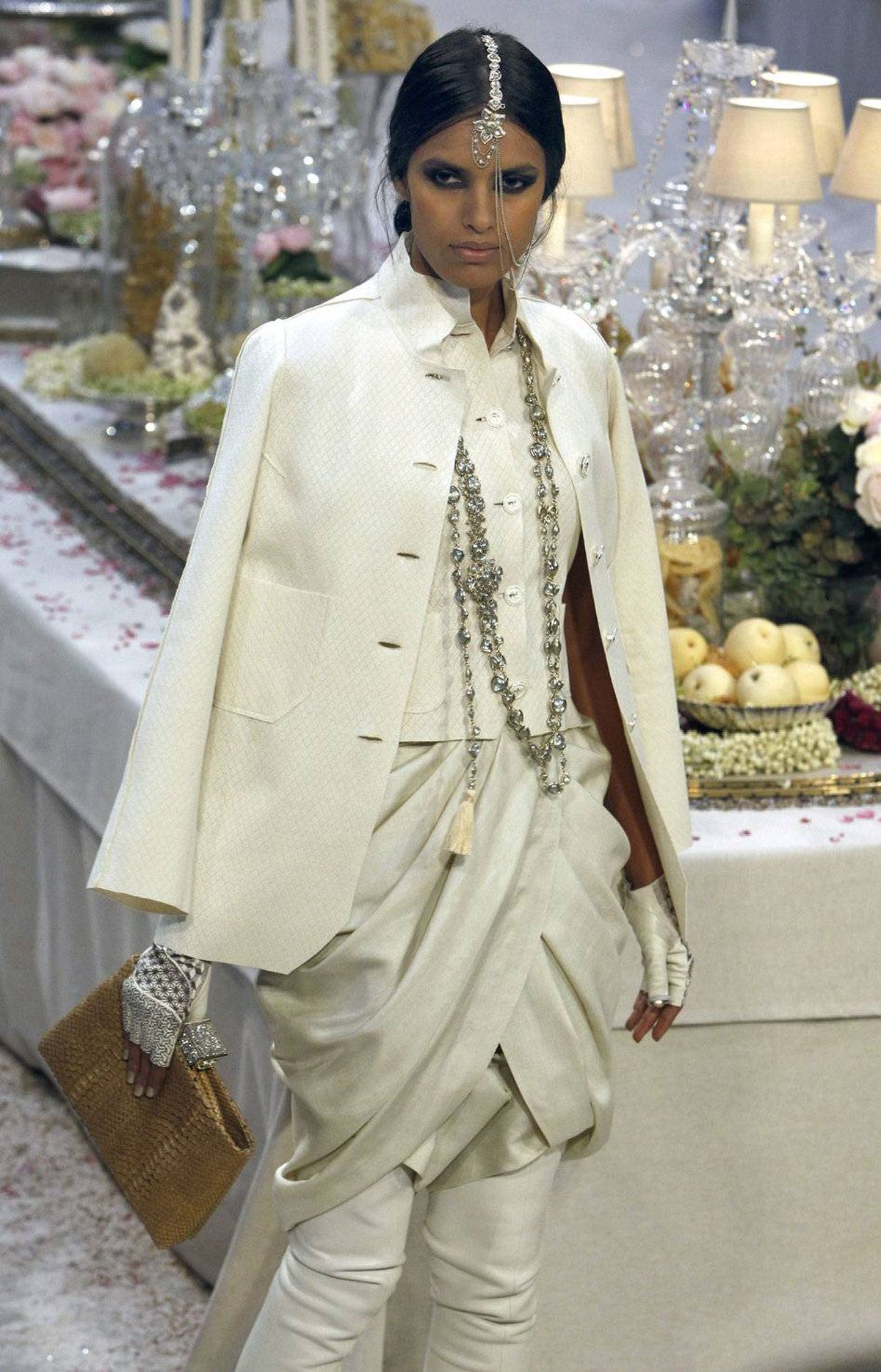 There is something particularly decadent about this all ivory everything statement. Better still, the metal-embellished, fingerless gloves. Note the jacket tossed over the outfit. Such insouciant chic!
