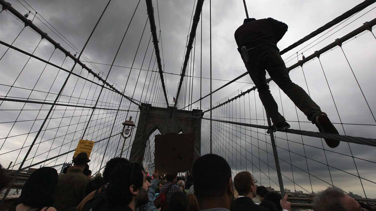 A man scales Brooklyn Bridge support cables during the Occupy Wall Street protests on Oct. 1, 2011.