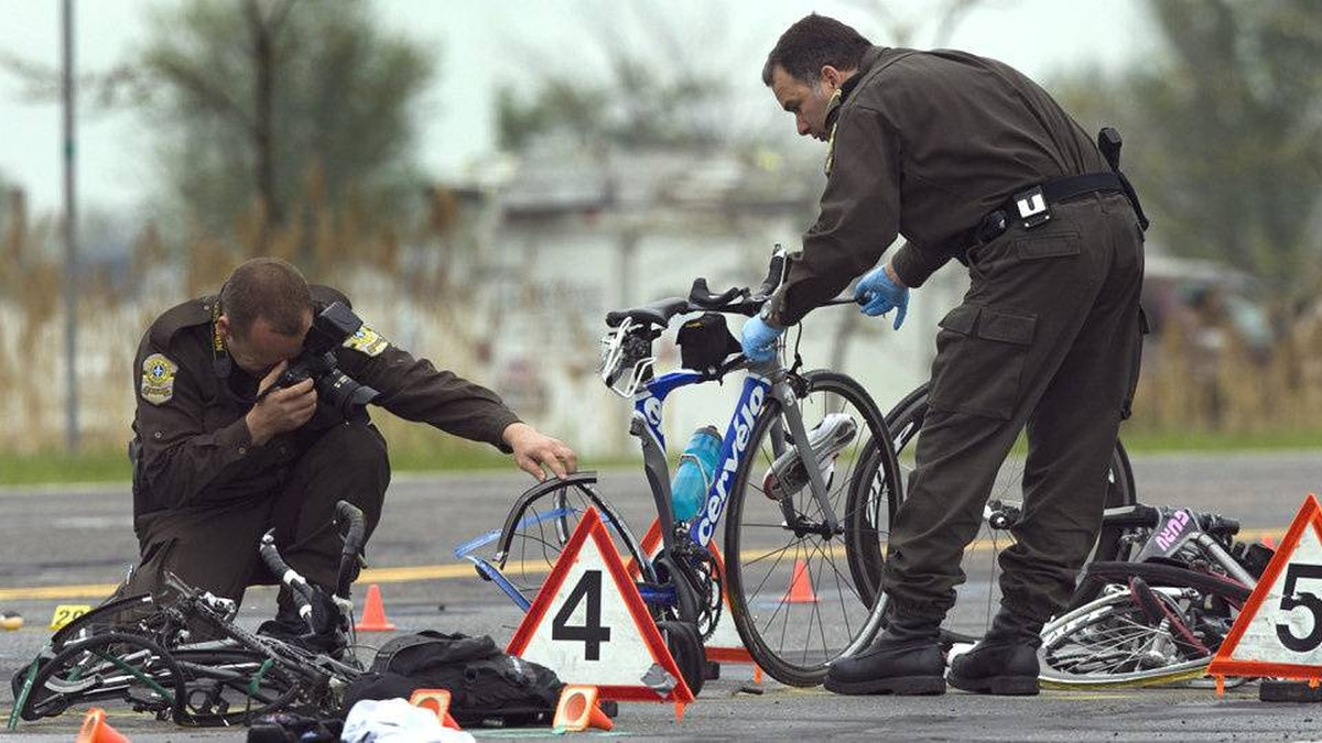 Police examine the scene where a pickup truck plowed into a group of cyclists Friday, May 14, 2010, in Rougemont, Quebec, south of Montreal.