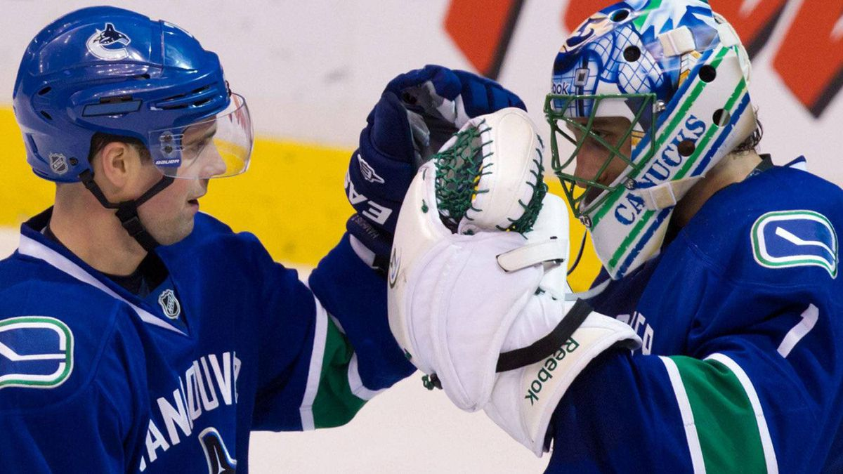 Vancouver Canucks' Dan Hamhuis, left, and goalie Roberto Luongo celebrate their win over the Minnesota Wild during an NHL hockey game in Vancouver, B.C., on Wednesday January 4, 2012. Luongo earned a shutout while playing in his 700th NHL game in the team's 3-0 victory over the Wild. THE CANADIAN PRESS/Darryl Dyck