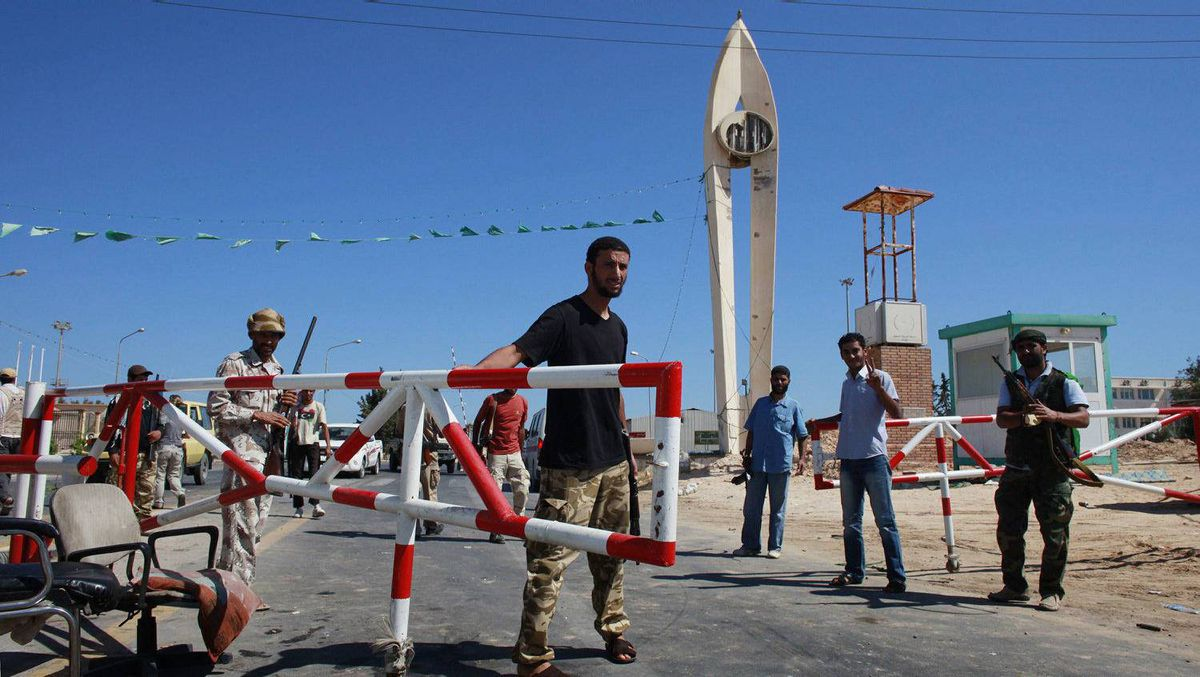 Libyan rebel fighters stand guard at the entrance to the Zawiyah oil refinery after they seized control of the complex, Aug. 18, 2011.