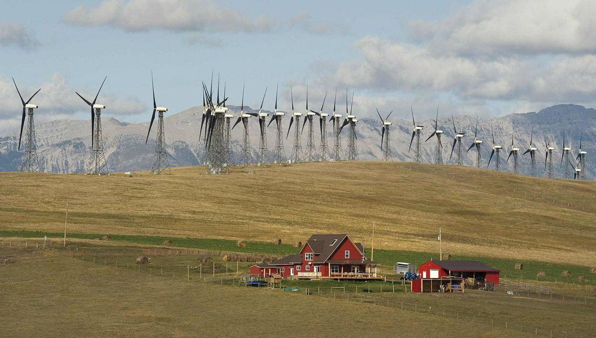 A ranch house sits below a wind farm generating electricity in the foothills of the Rocky Mountains near the town of Pincher Creek, Alta.