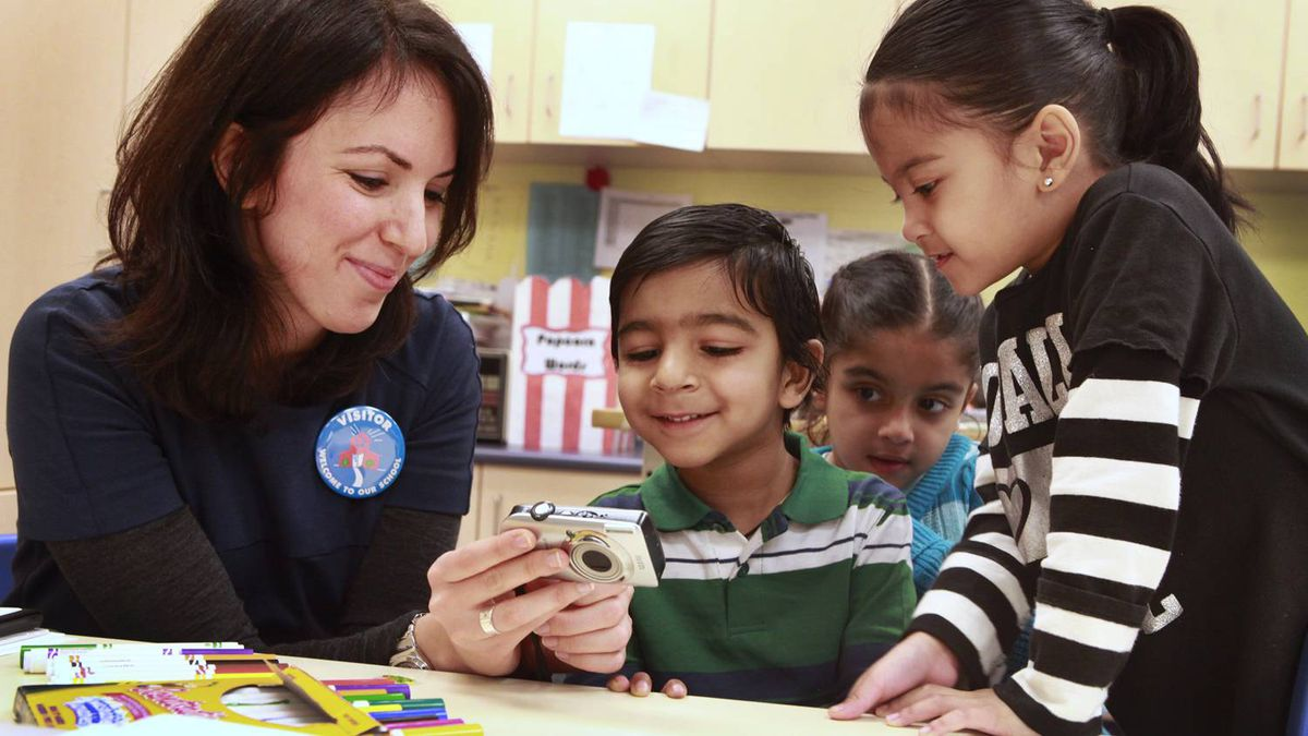Prathmesh Mistry (centre) reviews photos of his favourite things in his Junior Kindergarten class with researcher and OISE graduate student Kadria Simons(left)