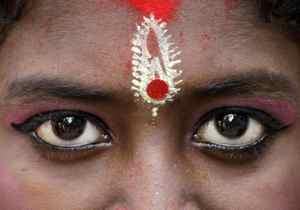 "A young Hindu girl dressed as ""Kumari"", or living goddess, pauses at a ceremony during the Hindu festival of Ram Navami in Kolkata, India, Sunday, April 1, 2012."