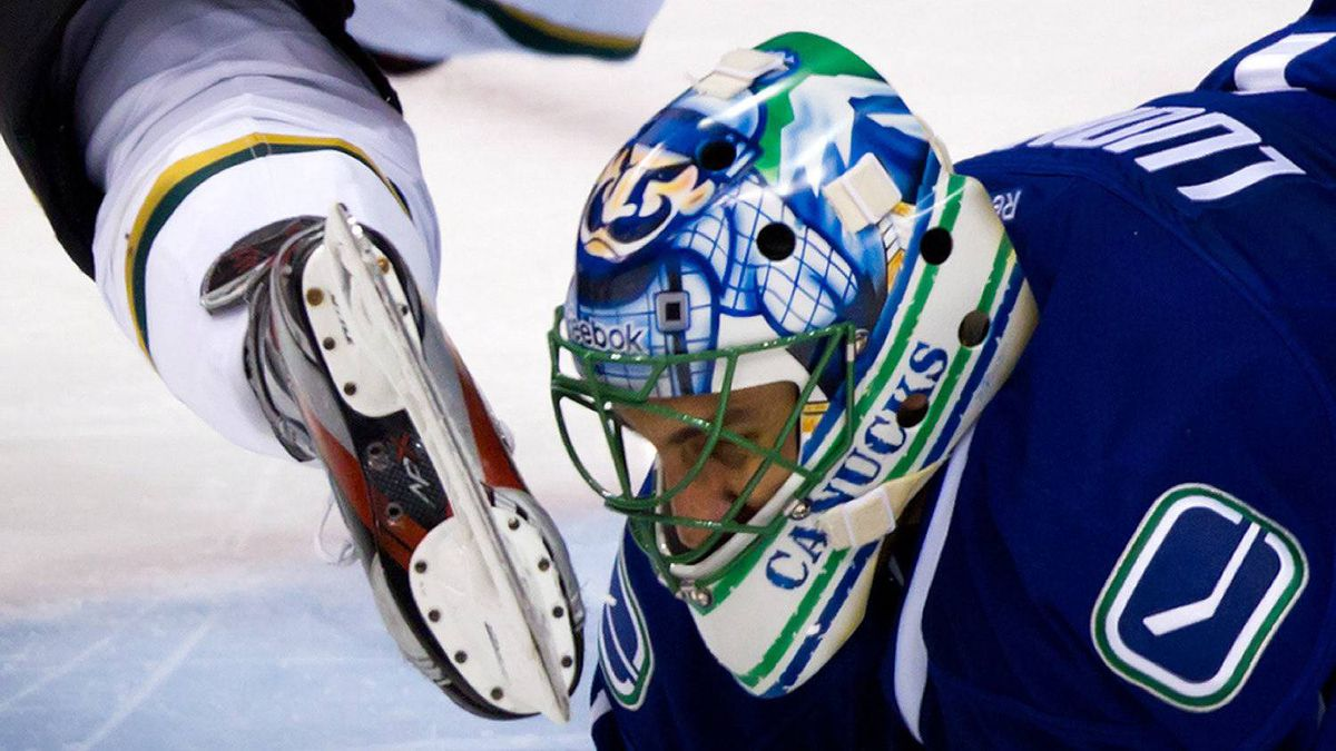 Vancouver Canucks goalie Roberto Luongo is nearly hit in the mask by the skate of Dallas Stars' Adam Burish after he tripped over Luongo during the third period of an NHL game in Vancouver on March 6, 2012.