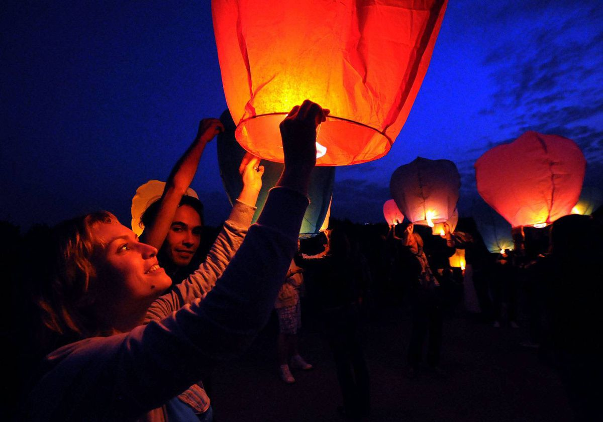 In this photo, taken on late Saturday, May 20, 2012, youths launch paper lanterns into the air just outside Moscow, Russia.