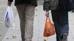 Shoppers hold Tesco and Sainsbury's supermarket carrier bags in London October 5, 2011.