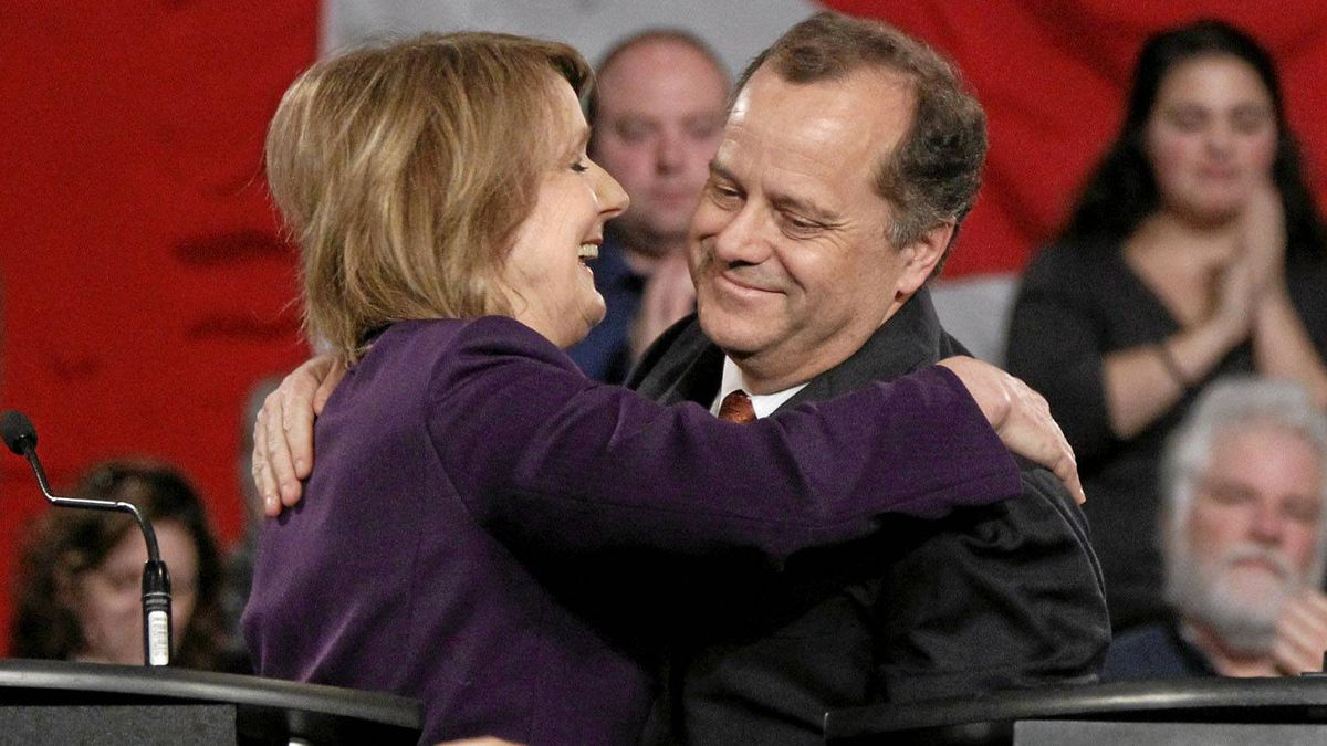 New Democratic Party Member of Parliament Peggy Nash (left) and party president Brian Topp embrace following the NDP leadership debate in Ottawa.