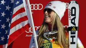 Lindsey Vonn, of the United States, celebrates while holding an American flag on the podium following her victory in the women's World Cup Super-G ski race event in Lake Louise, Alta., Sunday, Dec. 4, 2011.THE CANADIAN PRESS/Jeff McIntosh