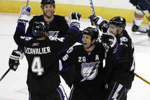 Tampa Bay Lightning's Martin St. Louis, centre, celebrates his game-winning goal with teammates Vincent Lecavalier, Ryan Malone, and Andrej Meszaros, against the Edmonton Oilers in Winnipeg, Thursday, September 24, 2009.