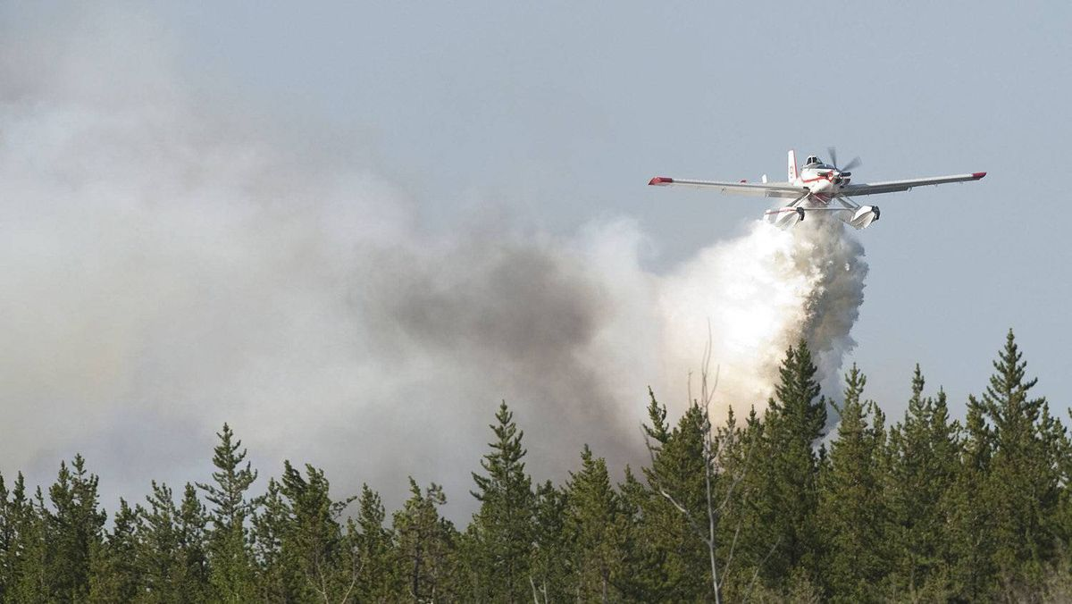 A water bomber drops it's water on a fire, 160 km northeast of Edmonton, Alberta, on Sunday May 15, 2011. Over a thousand people were ordered to leave their homes on Sunday when strong winds fanned two separate wildfires that burned on either side of a northern Alberta town.