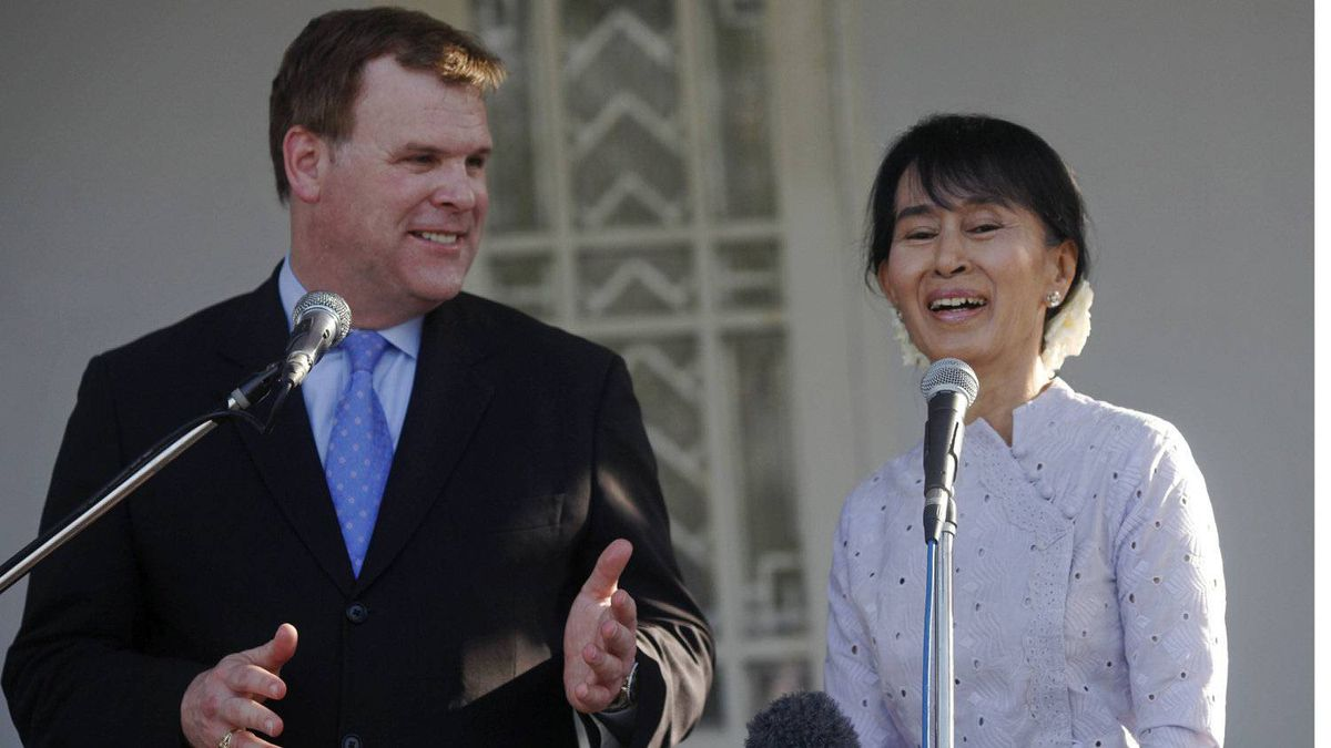 Myanmar's pro-democracy leader Aung San Suu Kyi , right, smiles as Canadian Foreign Minister John Baird talks to reporters after their meeting at her home in Yangon March 8, 2012.