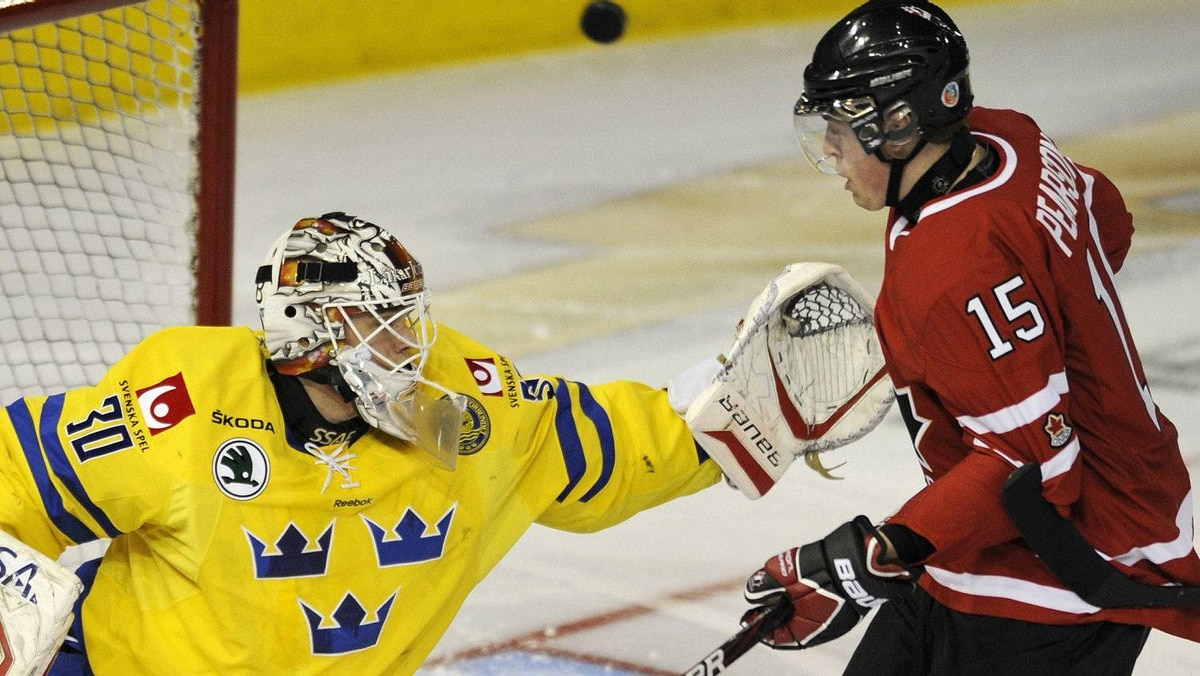 Team Sweden goalie Johan Gustafsson (L) and Team Canada's Tanner Pearson battle for the puck during the first period of their exhibition hockey game in Edmonton December 23, 2011.REUTERS/Dan Riedlhuber