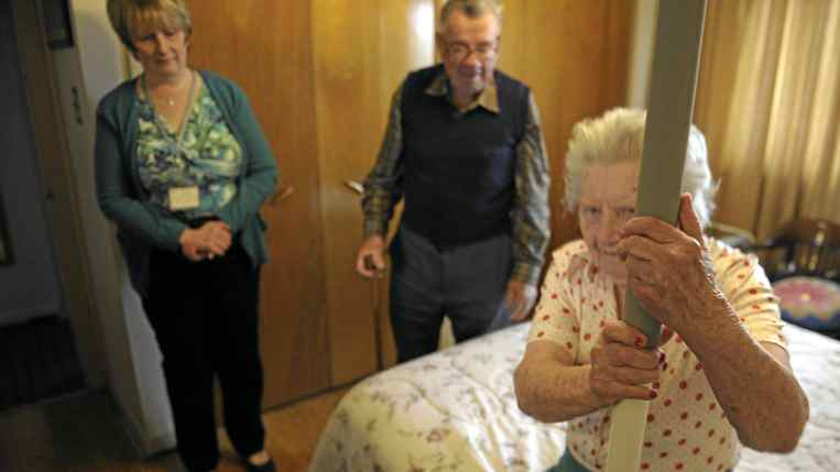 Katharina Lackner, 84, uses a special pole to help her get into and out of bed. Having taken a number of falls , her home is in the process of being evaluated to help prevent future falls. Nurse practitioner Anne Stephens and Katharina's husband Norbert, watch as she climbs into bed.(