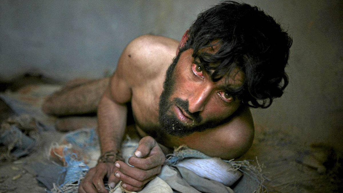 In this Oct. 7, 2009 photo, an Afghan opium addict, who has lost his mental balance, looks on as he is chained to the wall at the Mia Ali Baba Shrine, on the outskirts of Jalalabad, east of Kabul, Afghanistan.