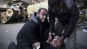 An injured anti-government protester is administered first aid in front of army vehicles during clashes in Tahrir, or Liberation square, in Cairo, Egypt, Wednesday, Feb. 2, 2011.