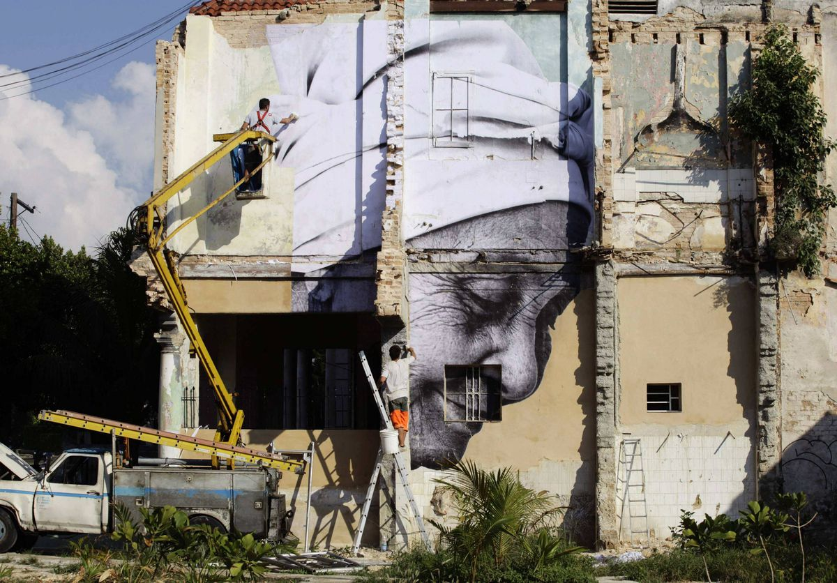 """Men put up a creation of Cuban-American artist Jose Parla and French artist J.R. on a building in Havana for the upcoming 11th Havana Biennial contemporary art exhibition. The project, titled """"Wrinkles Of The City"""", involves combining J.R's pictures of Cuban elderly people in the neighbourhood with Parla's calligraphic messages, and then pasting them on walls around the city."""