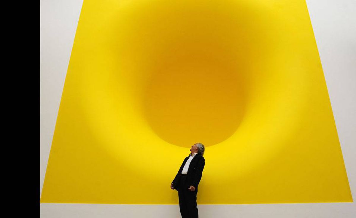 British artist Anish Kapoor poses for a photograph with his sculpture 'Yellow' at the Royal Academy of Arts in London September 22, 2009. The gallery is holding a major retrospective of Kapoor's work.