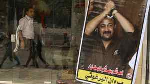 Members of Hamas national security forces are reflected in a souvenir shop window with a poster of jailed Fatah leader Marwan Al-Barghouti as they patrol a street to celebrate a prisoner swap between Hamas and Israel, in Gaza City October 12, 2011.