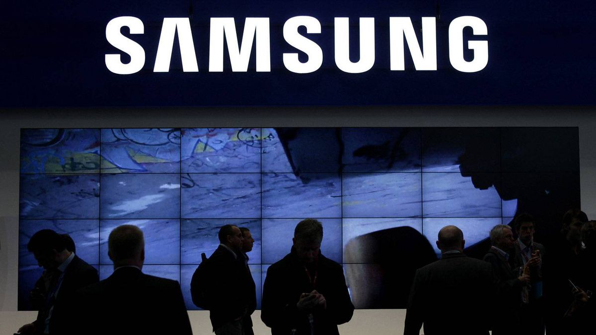 Visitors walk past the Samsung area at the GSMA Mobile World Congress in Barcelona, in this file picture taken February 14, 2011.