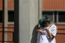 Medical wokers hug eachother outside the emergency rooms at Severo Ochoa Hospital during the coronavirus disease (COVID-19) outbreak in Leganes, Spain, March 26, 2020. REUTERS/Susana Vera