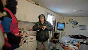 A man in Attawapiskat tries on gloves delivered by the Canadian Red Cross.