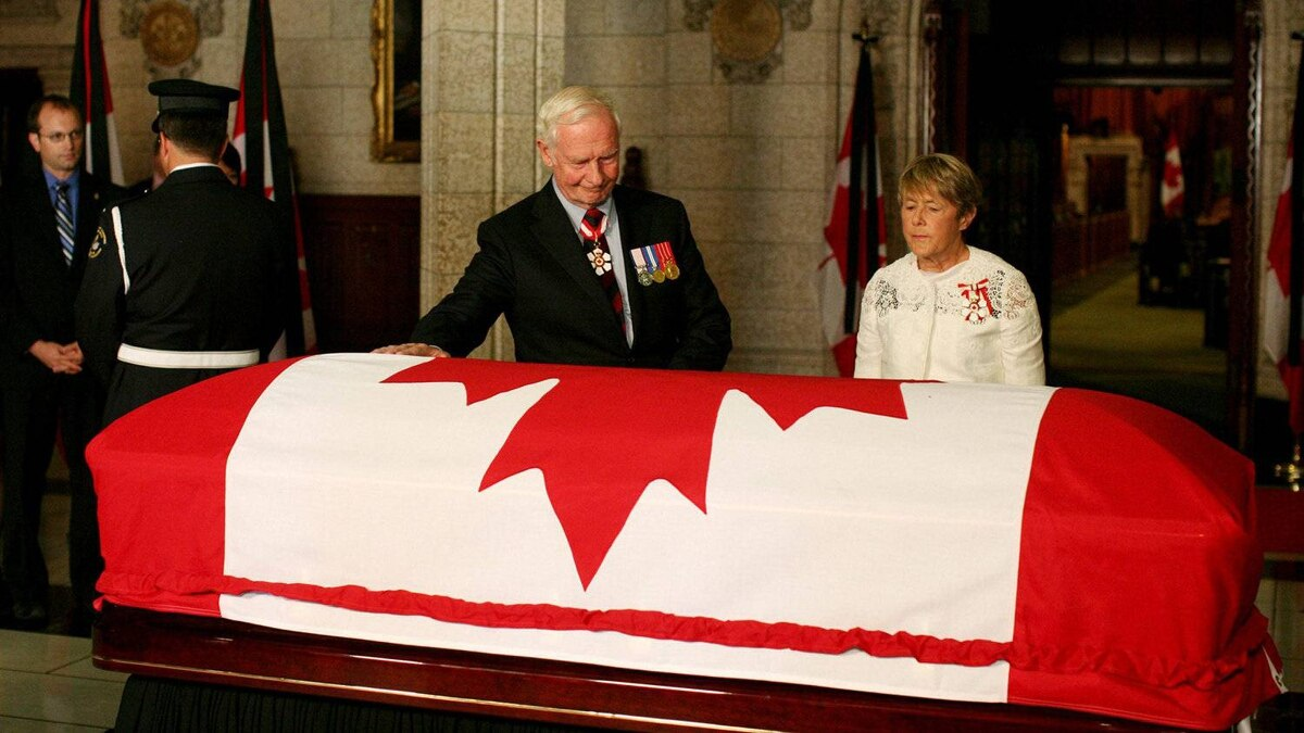Governor-general David Johnston touches the casket of Mr. Layton on Parliament Hill in Ottawa as his wife Sharon looks on.