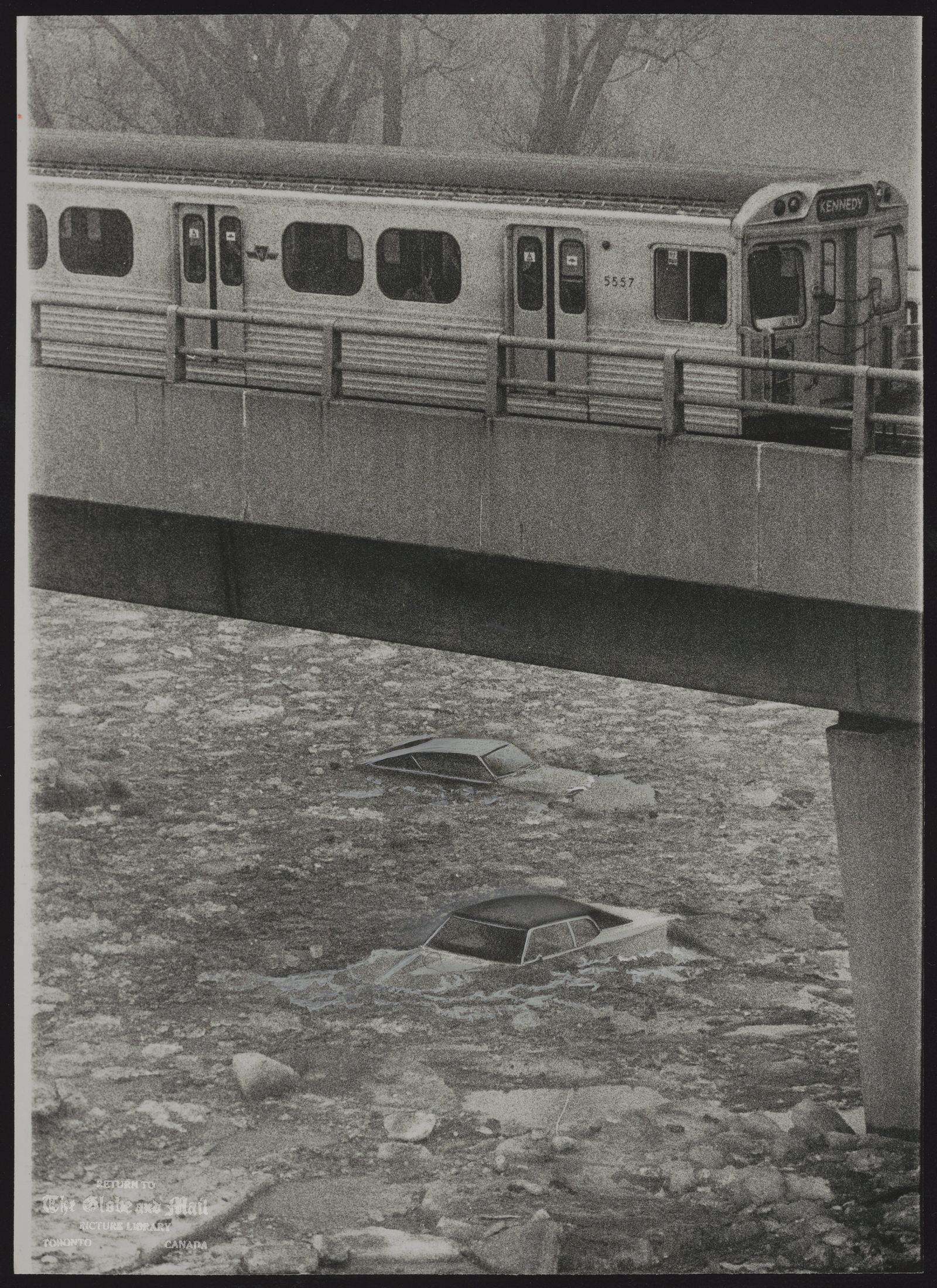 The notes transcribed from the back of this photograph are as follows: A subway train passes two cars almost submerged by ice and water in a parking lot at Toronto's Kings Mill Park. The early thaw caused the Humber River to flood its tanks.